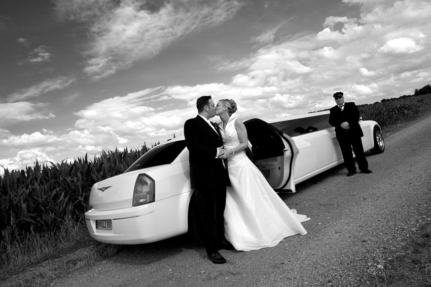 Bridal couple and limo at corn field