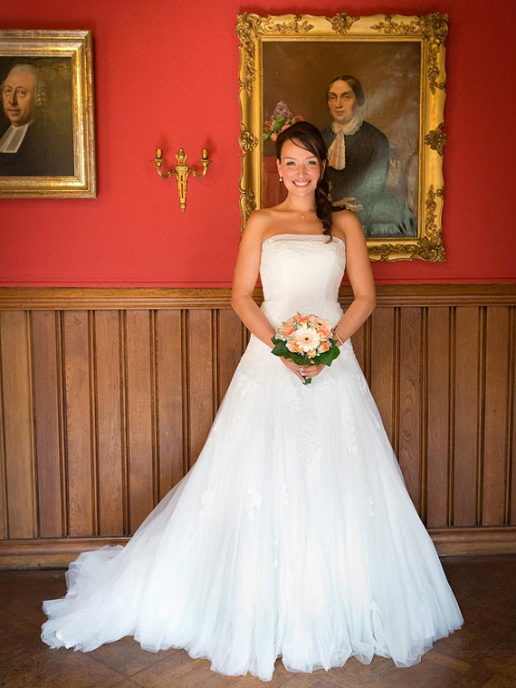 Bride posing in front of an old painting