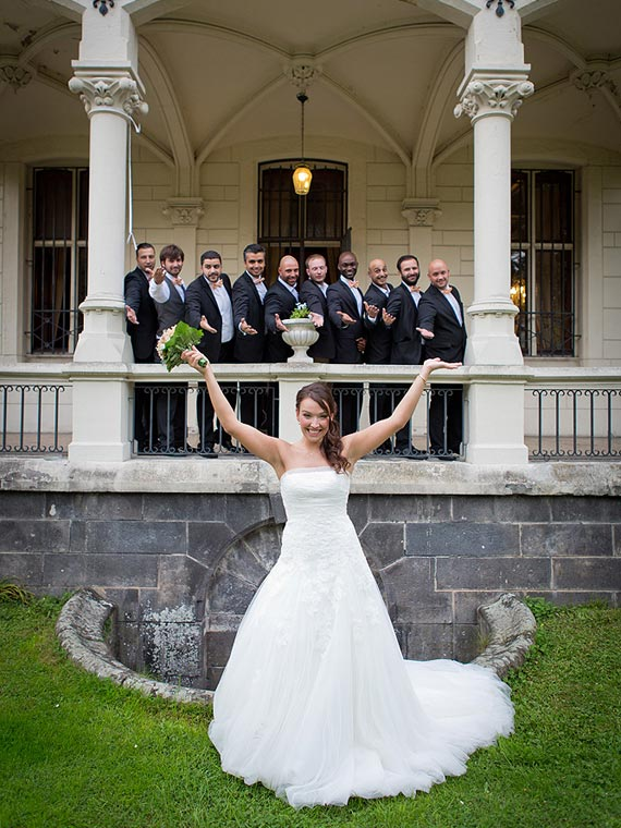 Bride throwing arms in the air, with groom & groomsmen