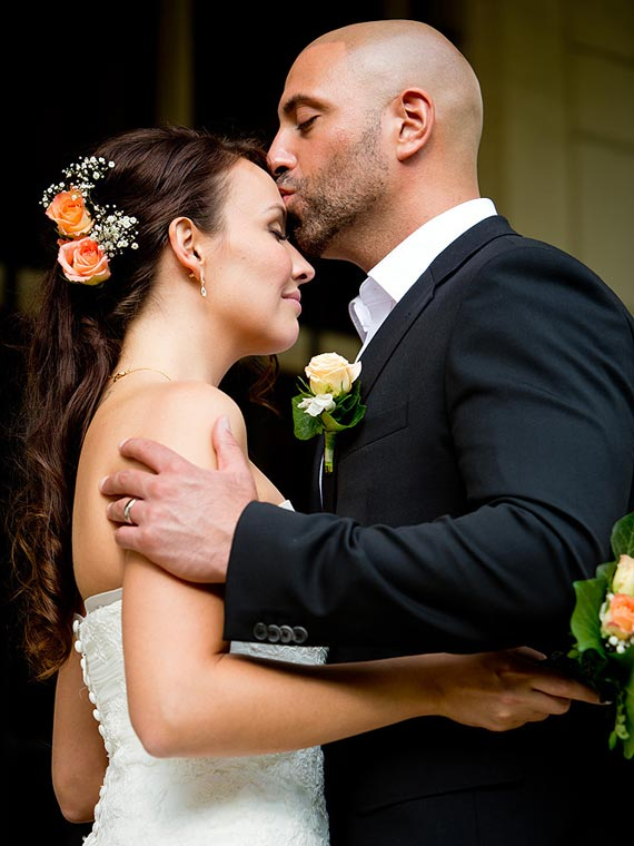 Groom kissing the forehead of his bride tenderly